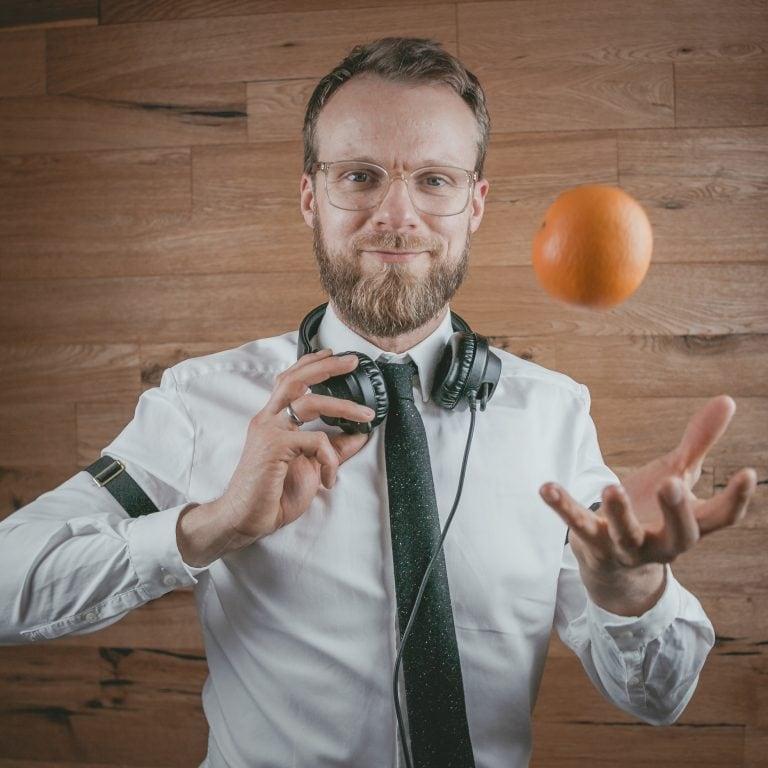 Event DJ aus Berlin Greg Oorange mit Orange vor Holzwand